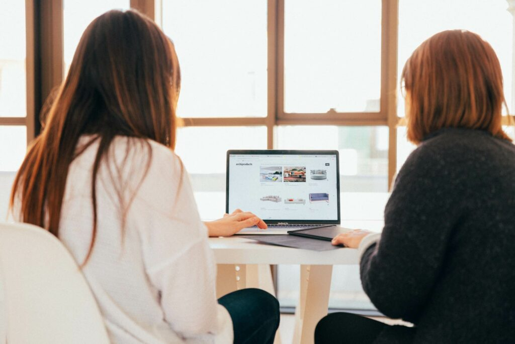Two women sat working together at a laptop in a work space