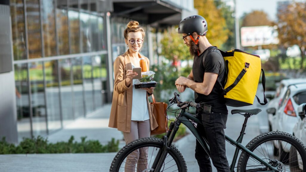 Delivery rider dropping off food to woman outside office