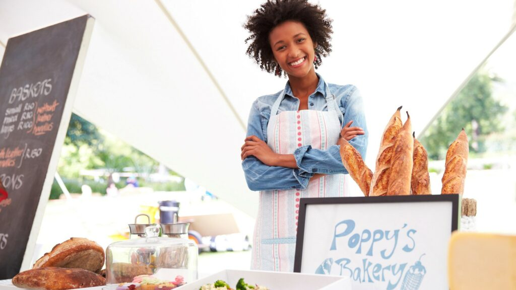 Female business owner stood in front of pop up stall selling baked goods