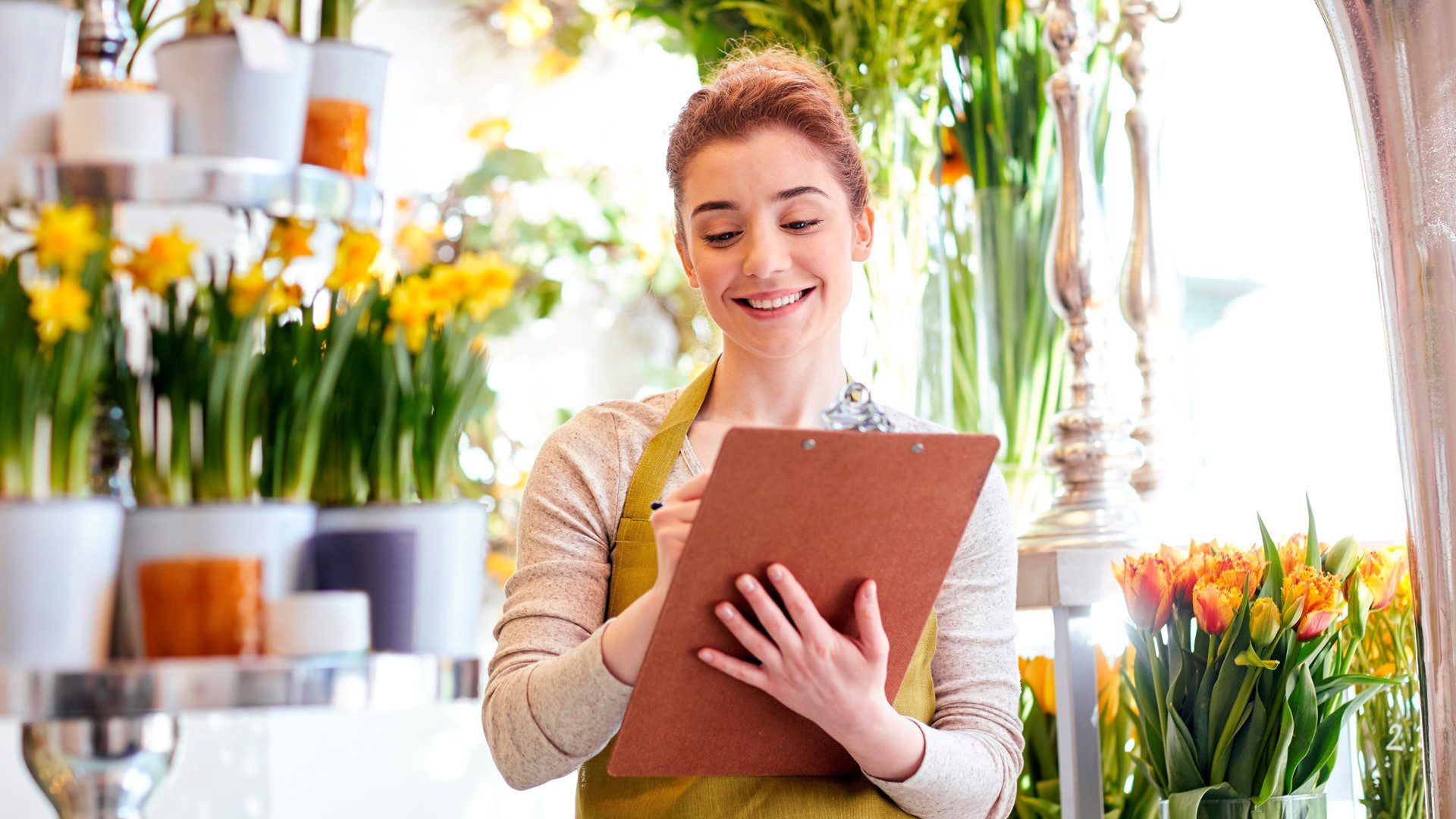 Woman marking items on a clipboard in a flower shop