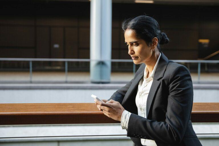 Businesswoman in dark suit using smartphone