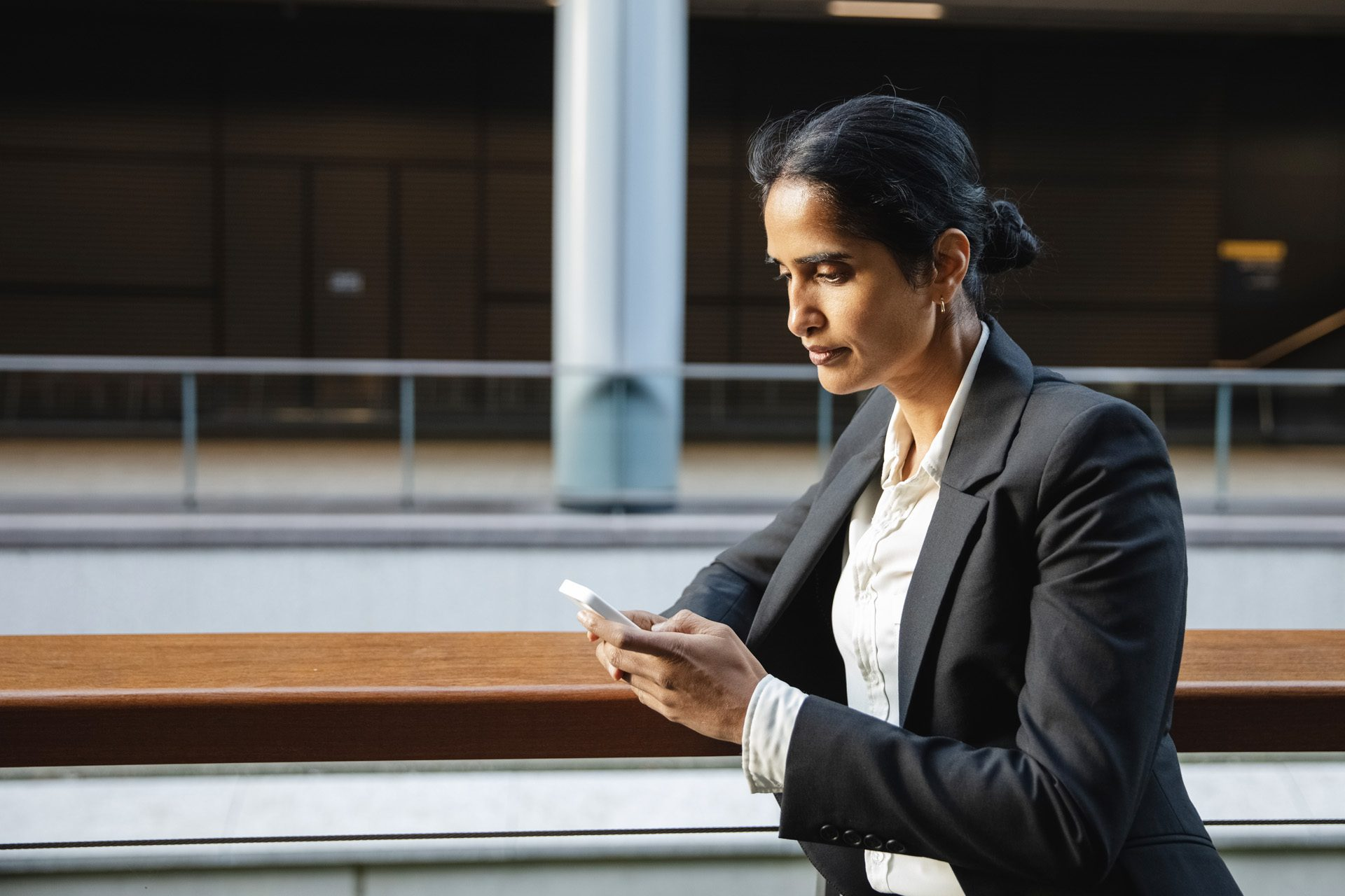 Businesswoman in dark suit using smartphone