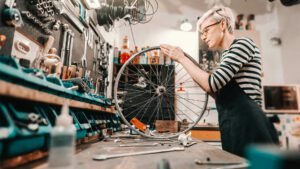 A woman in a workshop fixing the wheel of a bike
