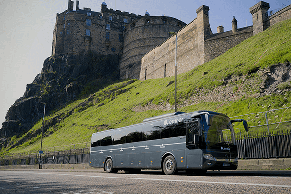 Ember's electric bus travelling down the road, with Edinburgh Castle in the background