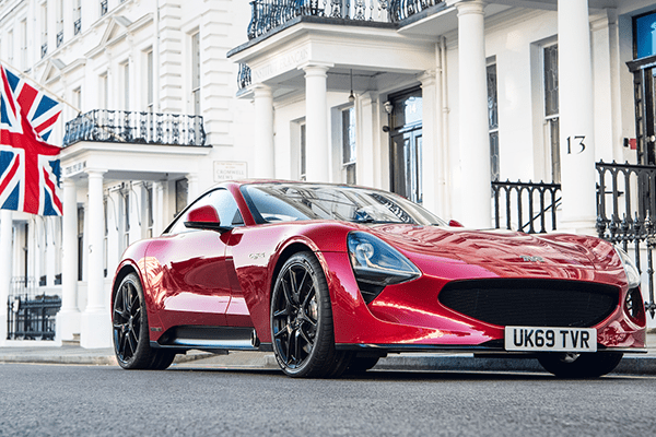 A red TVR Griffith sports car parked on an affluent-looking city street
