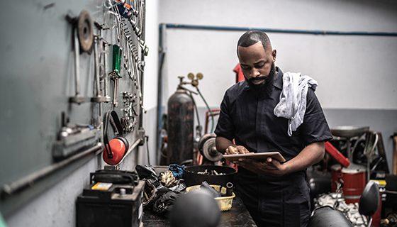 Engineer in workshop scrutinising tablet device
