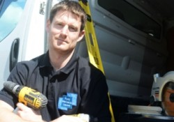 A man holding an electric drill next to a van