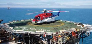A helicopter landed on a helipad with the ocean in the background