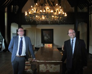 2 men stood in an dimly lit room with a long table and grand chandelier