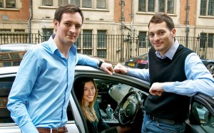 A woman sat in a car with 2 men stood next to her
