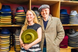 A man and a woman in a hat shop holding a hat with stacks of hats in the background