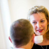 A woman talking to a man while holding a cup of tea