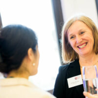 A woman wearing a BBB name tag smiling and talking to another woman