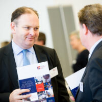 2 men in suits talking and holding The Vital Ingredient for Growth brochure