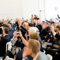 The audience at an event raising their hands while sitting down