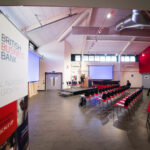 The Vital Ingredient for Growth event with a stage and chairs