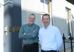 2 men stood outside a building smiling