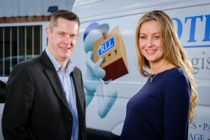 A man and a woman smiling and stood in front of a Rothwell Logistics van