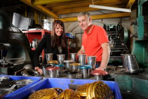 A man and a woman stood in a quality spun components manufacturer surrounded by equipment