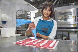 A woman in a commercial kitchen piping macaroons