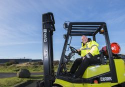 A man wearing a Hi Vis jacket and sat in a fork lift truck