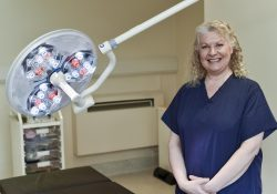 A woman stood in a treatment room with cosmetic surgery equipment next to her