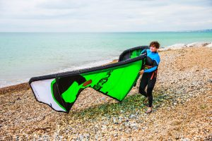 A person carrying a windsurf on a rocky beach