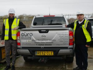 2 men in Hi Vis jackets and hard hats from Euro Recycling Broker stood next to a branded car