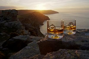 A glasses of whiskey with ice resting on a ledge overlooking the ocean and sunset