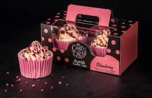 A box of 2 strawberry cupcakes and one extra cupcake sitting next to the box