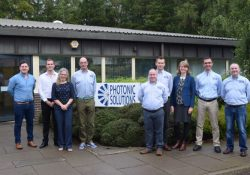 Photograph of Photonic Solutions workforce stood next to a Photonic Solutions sign