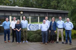 A group of employees stood in front of the Photonic Solutions office