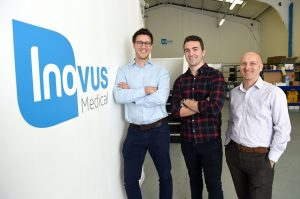 3 men stood near an Inovus Medical branded wall with office equipment in the background