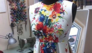 A close up of a floral dress on a mannequin with a sewing machine and threads in the background