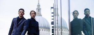 A man and a women dressed in black posing next to a glass building with St Pauls Cathedral in the background