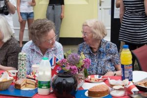 2 women sat at a union jack themed table having tea and cake whilst chatting