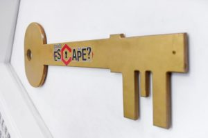 A large key on the wall with the word Can You Escape written on it