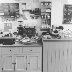 A coffee shop counter with cakes, coffee machine and menu