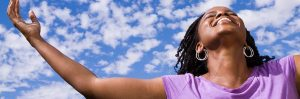 Woman in a purple t-shirt smiling looking up to the sky