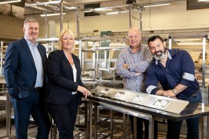 3 men and a women stood in a kitchen surrounded by metal catering equipment