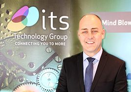 A man in a suit smiling in front of a ITS Technology Group branded wall