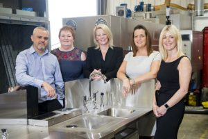 A man and four women in a warehouse environment stood around a sink area