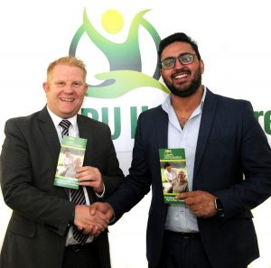 2 men in suits shaking hands and holding Aru Home Care leaflets with the logo on the wall behind them