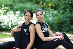 The two female founders of ace lifestyle sat back to back in a park setting