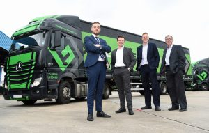 4 men in suits stood in front of a Mercedes Benz lorry