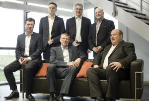 A group of men in suits sat and stood around a couch in an office building