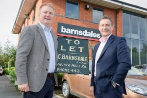 2 men stood outside of the Barnsdales office holding a To Let sign