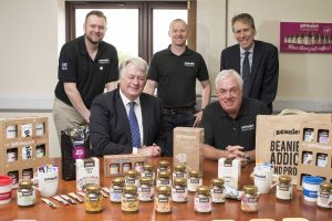 5 men gathered around a table of Beanies Flavour Coffee products