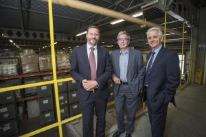 3 men in suits smiling in a warehouse with stacks of boxes in the background