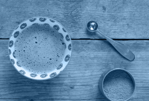 A cup of tea on a wooden table with a metal spoon next to it